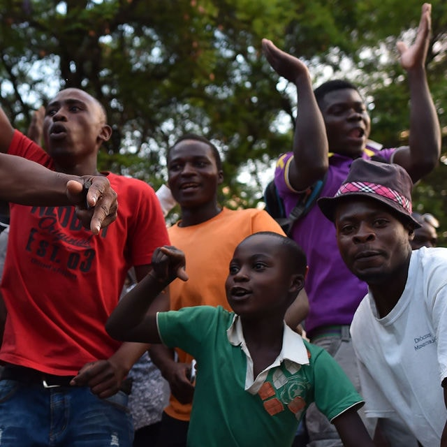People celebrate in the streets of Harare, after the resignation of Zimbabwe's president Robert Mugabe on November 21, 2017. The bombshell announcement sparks scenes of wild celebration in the streets of Harare, with car horns honking and crowds dancing and cheering over the departure of the autocrat who has ruled Zimbabwe since independence. / AFP PHOTO / Tony KARUMBA