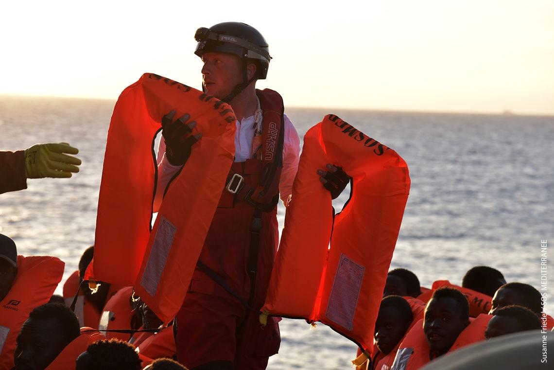 Ein Helfer verteilt Rettungswesten.