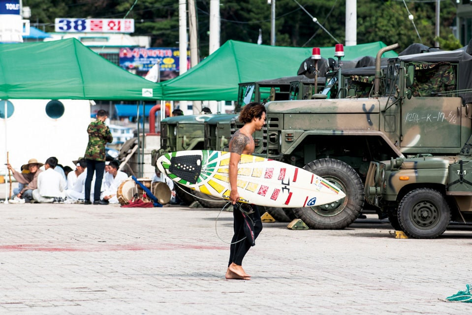 Junger Südkoreaner mit Surfboard.