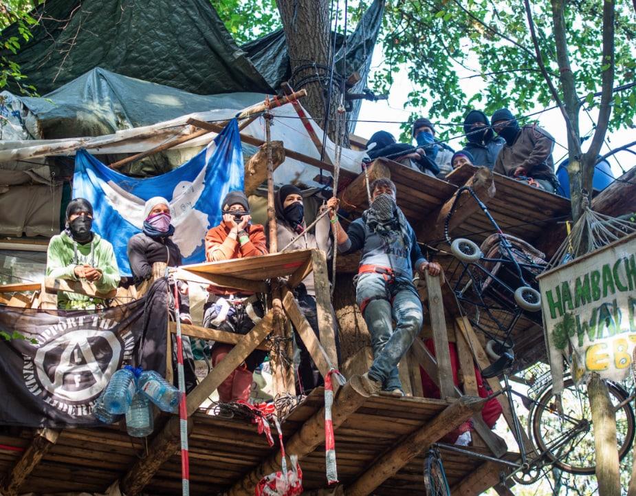 Aktivisten stehen im Hambacher Forst auf einem Baumhaus.