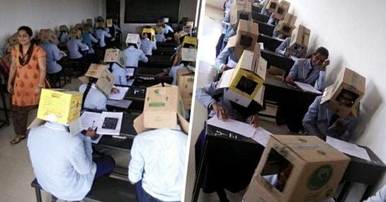 Studierende schreiben Examen mit Schachteln über dem Kopf
